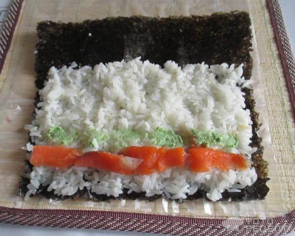 Ломтики лосося раскладываем на слой риса и смазываем васаби